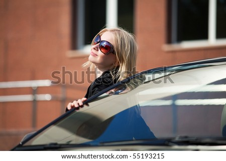 Young blonde with a her convertible car. - stock photo