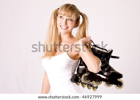 young blonde with white sportswear and plaits with roller skates on the shoulder - stock photo