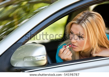 Young blonde woman applying makeup while in the car - stock photo