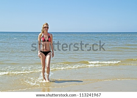 Young blonde woman coming out of the water from the ocean - stock photo