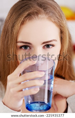 Young blonde woman drinking water - stock photo
