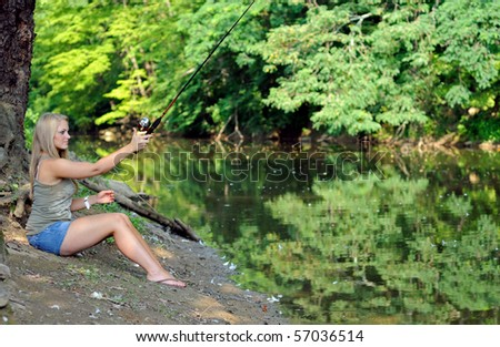 Young blonde woman fishing from bank of creek  - casting - stock photo