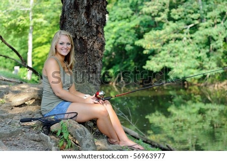 Young blonde woman fishing on creek bank - smiling - stock photo