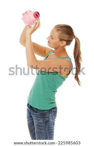 Young blonde woman holding piggybank - stock photo