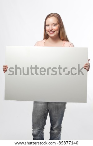 Young blonde woman holding sign - stock photo