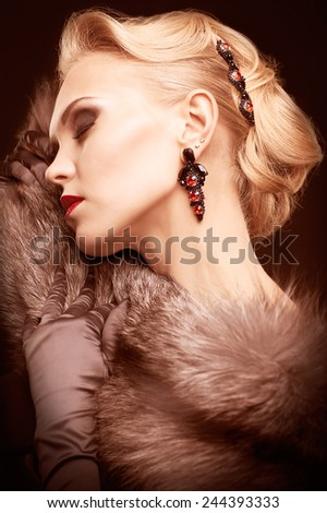 Young blonde woman in black dress and fur of silver fox on dark background toned in marsala color - stock photo