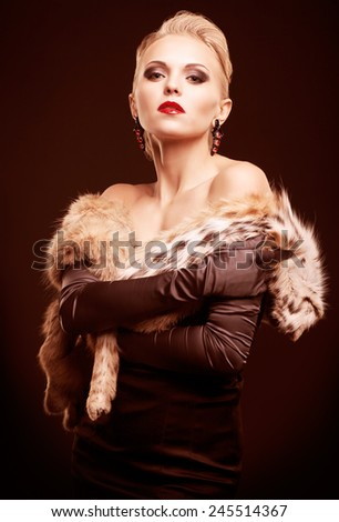 Young blonde woman in black dress and lynx fur with and long gloves on dark background toned in marsala color - stock photo