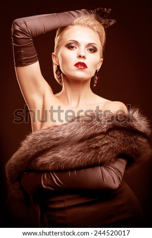 Young blonde woman in black dress and silver fox fur with and long gloves on dark background toned in marsala color - stock photo