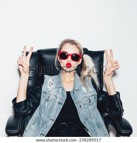Young blonde woman in sunglasses sit on black office chair and showing victory by finger. Fashoin hipster girl.  White background, not isolated - stock photo