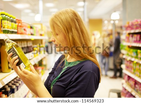 Young blonde woman in the supermarket is reading inscription on the juice bottle - stock photo