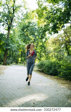 Young blonde woman jogging in park - stock photo