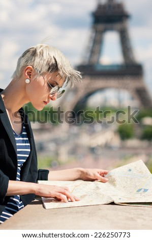 Young blonde woman looking at map of the city in front of the Eiffel Tower in Paris, France. Filtered image. - stock photo