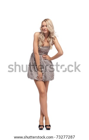 Young blonde woman posing in stylish dress - stock photo
