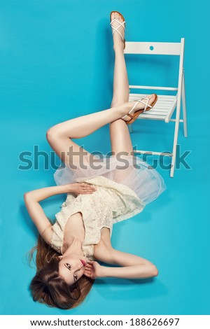 young blonde woman posing on a chair in white laced dress - stock photo