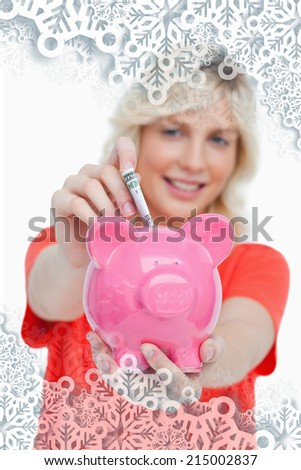 Young blonde woman putting notes into a pink piggy bank against snowflakes on silver - stock photo