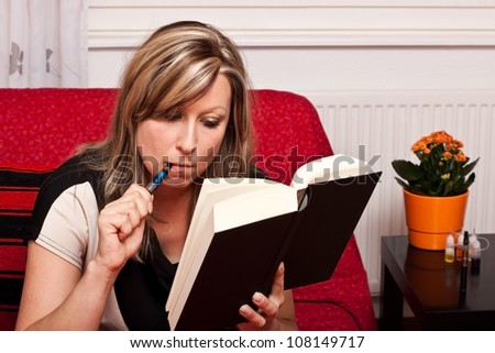 Young blonde woman reading a book, and evaporated to an electric cigarette - stock photo