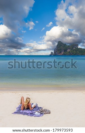 Young blonde woman reading a book on Phi Phi island beach in Thailand - stock photo