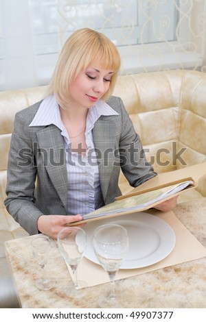 young blonde woman reading menu at first class restaurant - stock photo