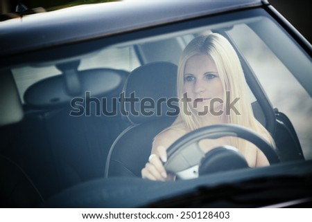 Young, blonde woman seen through a car windscreens sitting at the wheel and driving. - stock photo