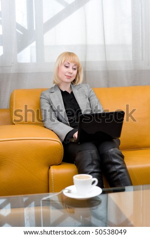 young blonde woman sits on leather sofa with laptop, in front of glass table with cup of coffee - stock photo