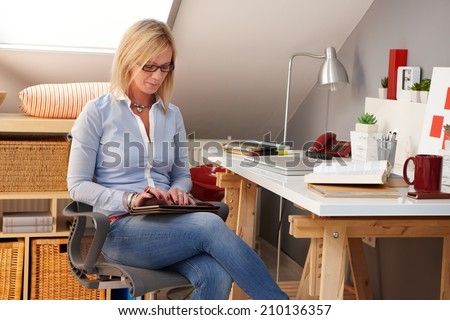 Young blonde woman sitting at home, using tablet computer. - stock photo