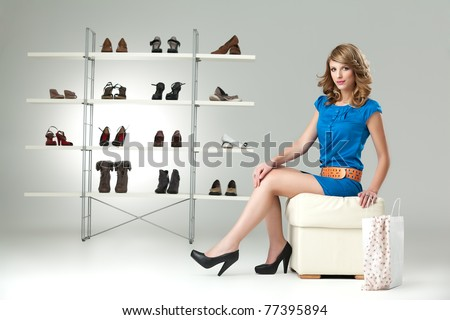 young blonde woman sitting down blue dress - stock photo