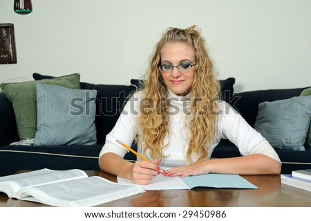 Young blonde woman sitting in living room with take home exam - stock photo