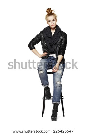 Young blonde woman sitting on high stool. Rock style. Isolated on white background. - stock photo