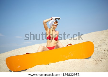 Young blonde woman sitting on sand with a snowboard in resort surroundings - stock photo