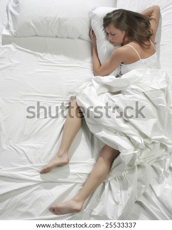 Young blonde woman sleeping in the bed - stock photo