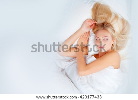 Young blonde woman sleeps in white bed - stock photo