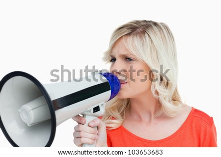 Young blonde woman speaking into a megaphone against a white background - stock photo