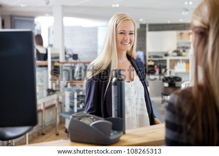 Young blonde woman standing by cash counter at hair salon - stock photo
