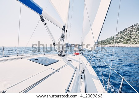 Young blonde woman wearing red shorts, sitting on deck under sails on yacht bow and enjoying wonderful view to cliffs in peaceful sea during summer sailing holidays - yacht charter concept - stock photo