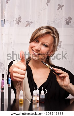 Young blonde woman with cigarette electrical equipment  lifts thumb up - stock photo