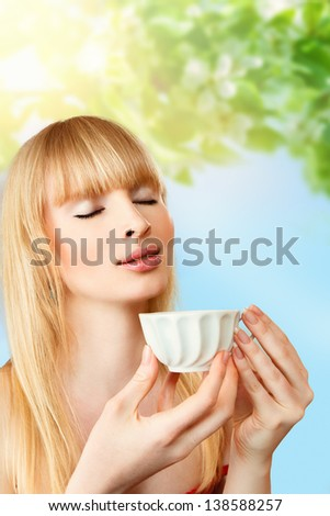 Young blonde woman with cup of herbal tea - stock photo
