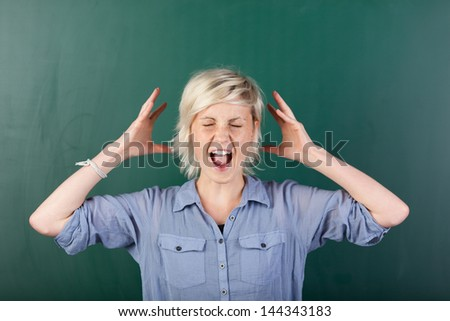 Young blonde woman with eyes closed shouting in front of chalkboard - stock photo