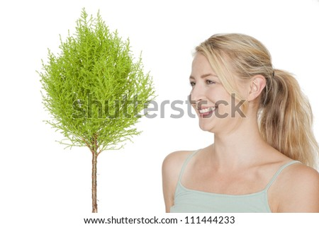 young blonde woman with green  bonsai tree - stock photo