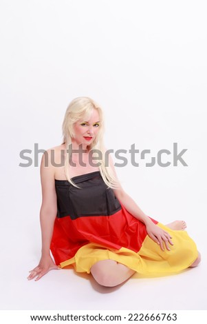Young blonde woman with long hair, naked, with Germany flag wrapped, sitting on the floor / Young woman wrapped naked with Germany flag - stock photo