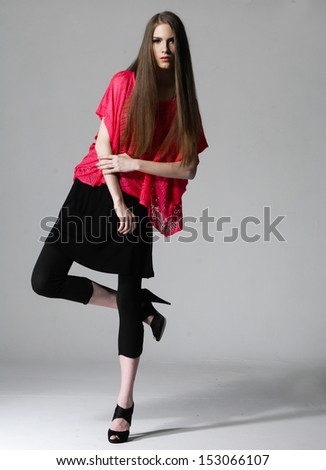 Young blonde woman with long hair posing in stylish dress - stock photo