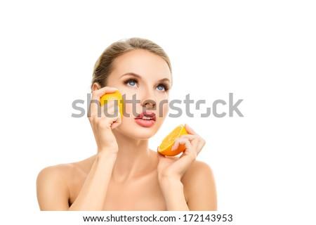 Young blonde woman with orange in her hands studio portrait isolated on white background - stock photo