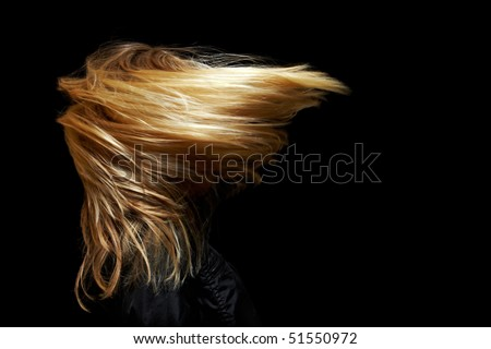 Young blonde woman with waving hair in the dark - stock photo