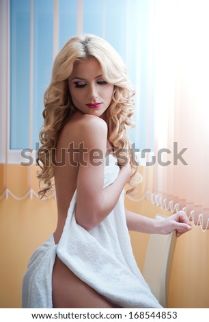 Young blonde woman wrapped in white towel posing relaxed. Beautiful young woman with a towel around her body after bath. Side view of long fair hair girl sitting on chair exposing her shoulder. - stock photo