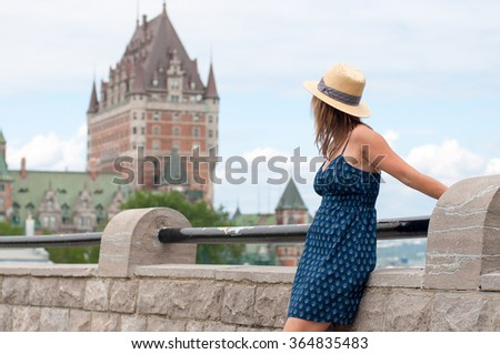 Young blonde women looking at the blurred Frontenac Castle in the background, Quebec, Canada - stock photo