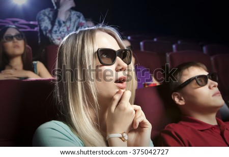 Young blonde women sitting at the cinema, watching a film. Cinema photo series - stock photo