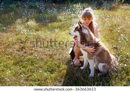 Young blondy woman with her huskey dog - stock photo
