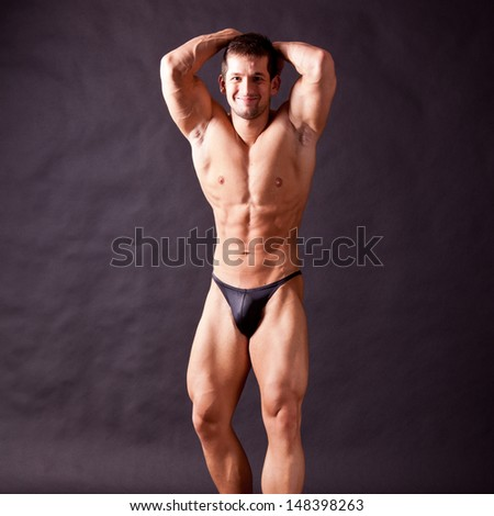 young bodybuilder posing in studio - stock photo