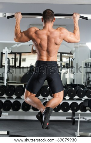 young bodybuilder training in the gym: back - Wide-Grip Front Pull-Up - stock photo