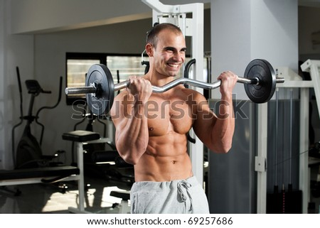 young bodybuilder training in the gym - e-z bar biceps curl - stock photo