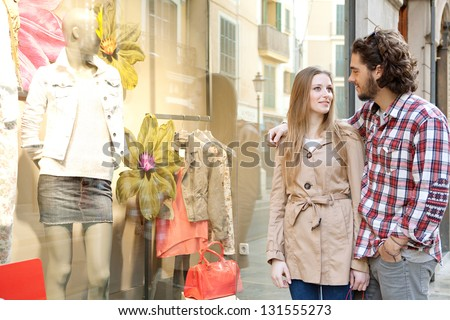 Young bohemian couple looking at clothes in a store window while on vacations in a destination city, smiling. - stock photo